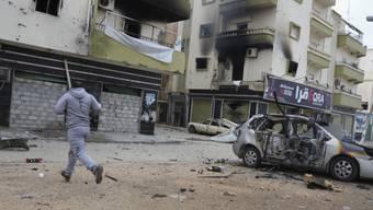 Mann rennt vor beschossenen Gebäuden in Benghasi (Archivbild)