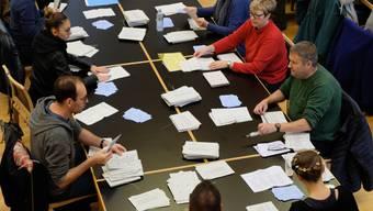 Wahlhelferinnen und Helfer zählen im Wahlbüro Dietikon (ZH) die Wahl- und Abstimmungszettel aus.
