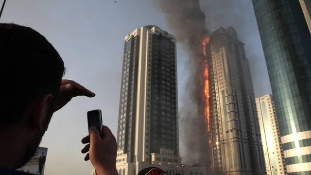 Ein Anwohner filmt das brennende Gebäude mit seinem Handy