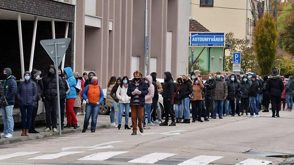 Zahlreiche Menschen mit Gesichtsmaske warten in einer Schlange, um sich auf das Coronavirus testen zu lassen. Foto: Edmund ÷rzsik/TASR/dpa