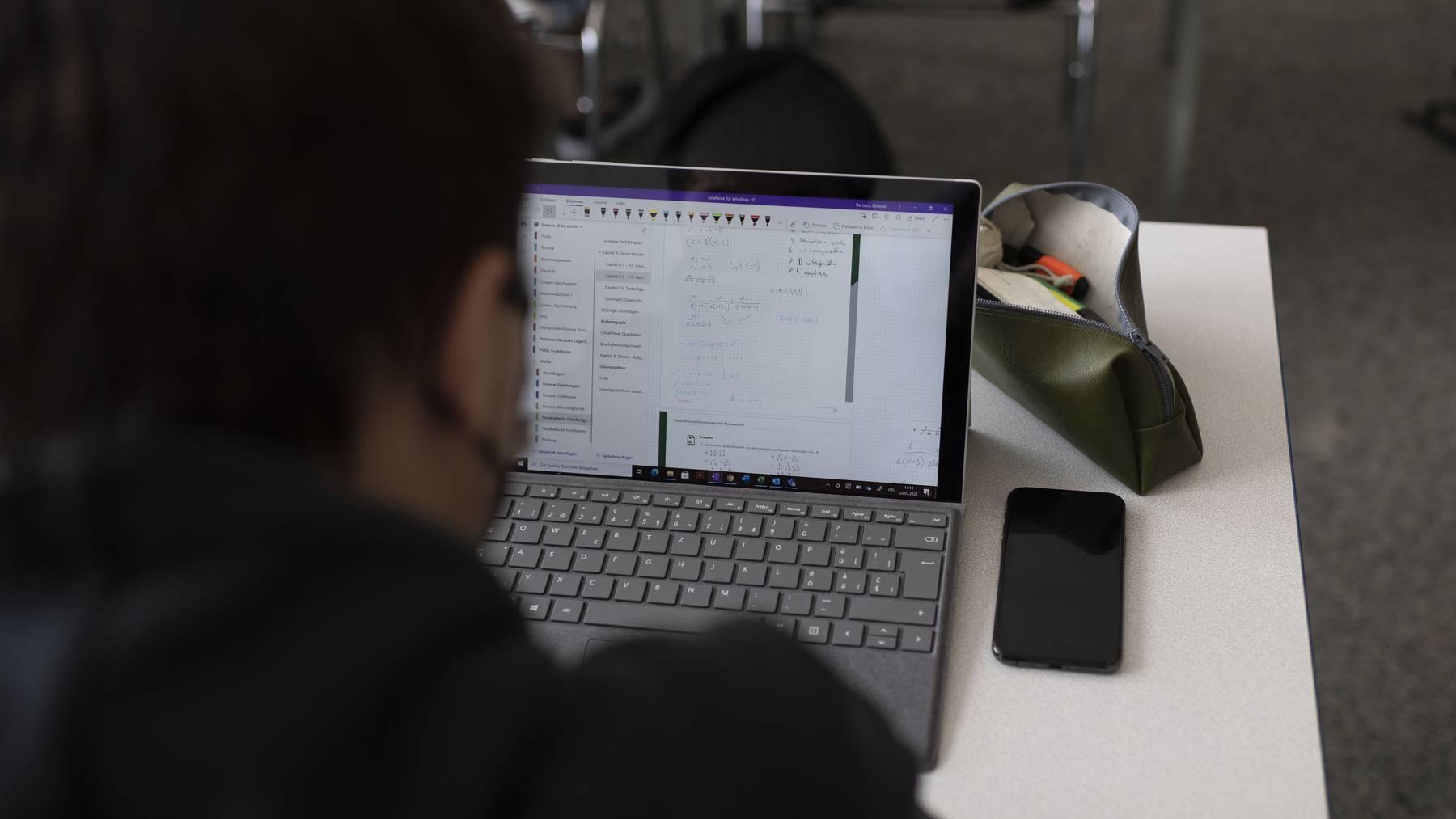 Ein Schueler der Klasse 21-M2.20 der Wirtschaftsschule KV Zuerich arbeitet Maske tragend selbststaendig am Laptop waehrend des Mathematikunterrichts, fotografiert am 25. Maerz 2021 in Zuerich.