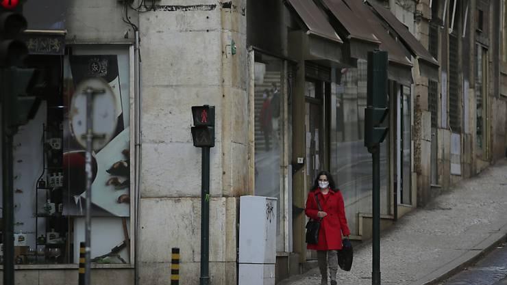 ARCHIV - Eine Frau mit Maske geht eine sehr ruhige Straße in der Innenstadt entlang. Foto: Armando Franca/AP/dpa