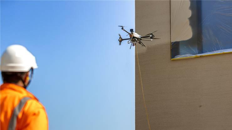 Eine Drohne des Zürcher Start-ups Voliro besprüht automatisch ein Gebäude.