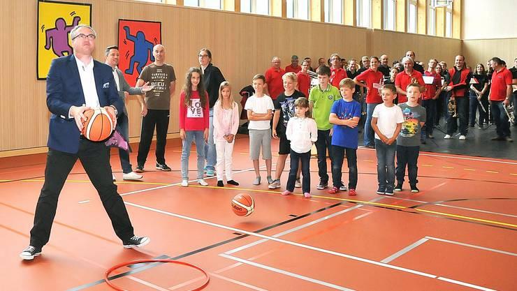 Statt dass ein Band durchschnitten wurde, wurde ein Korbwerfen veranstaltet: Regierungsrat Remo Ankli beim Wurf – mit Sakko und Sneakers.