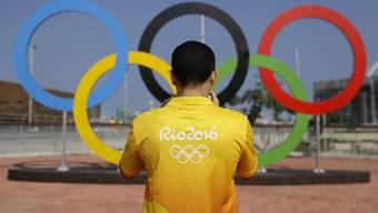 Ein freiwilliger Helfer fotografiert die olympischen Ringe im Olympia-Park in Rio.