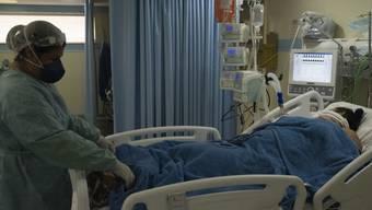 Eine medizinische Mitarbeiterin auf der Intensivstation eines Krankenhauses in Rio de Janeiro untersucht eine Patientin, die mit dem neuartigen Coronavirus infiziert ist. Foto: Ppi/PPI via ZUMA Wire/dpa
