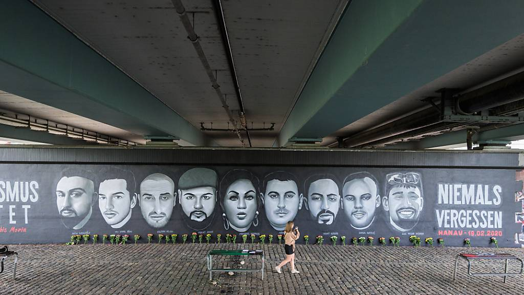 ARCHIV - Eine Frau geht vor Porträts von Opfern des Anschlags von Hanau entlang. Ein Gemälde unter der Frankfurter Friedensbrücke zeigt jetzt die Porträts von neun Opfer der Anschläge in Hanau. Foto: Andreas Arnold/dpa - ACHTUNG: Nur zur redaktionellen Verwendung im Zusammenhang mit der aktuellen Berichterstattung.