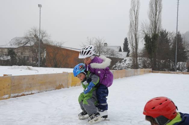 Grosse Schwester hilft kleinem Bruder.