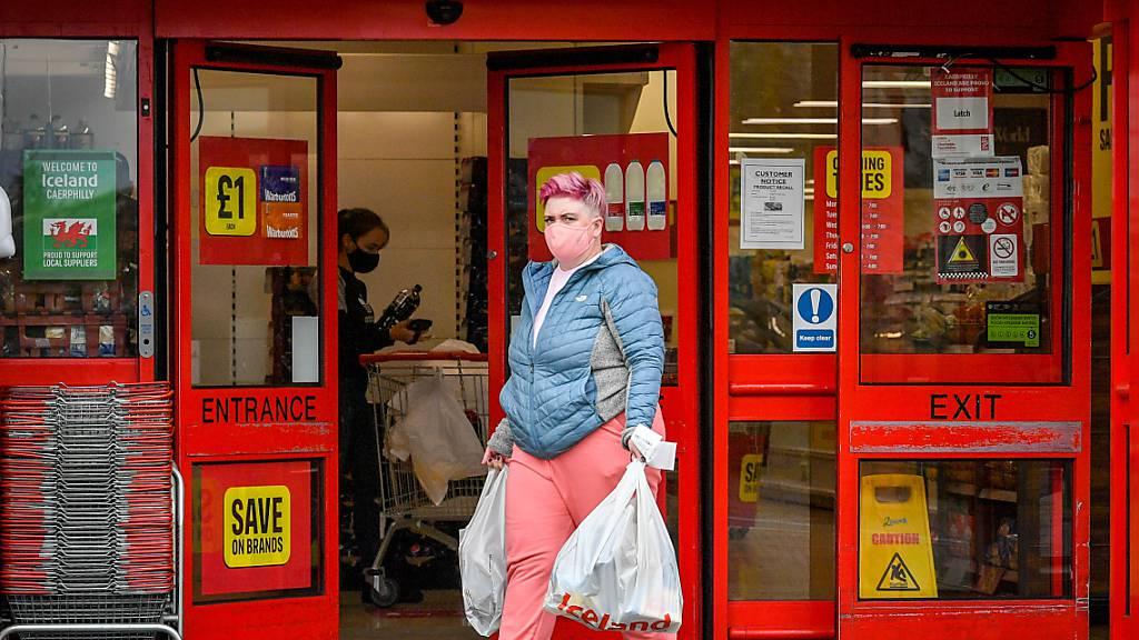 ARCHIV - Eine Frau mit Mundschutz verlässt einen Supermarkt im britischen Caerphilly. Foto: Ben Birchall/PA Wire/dpa