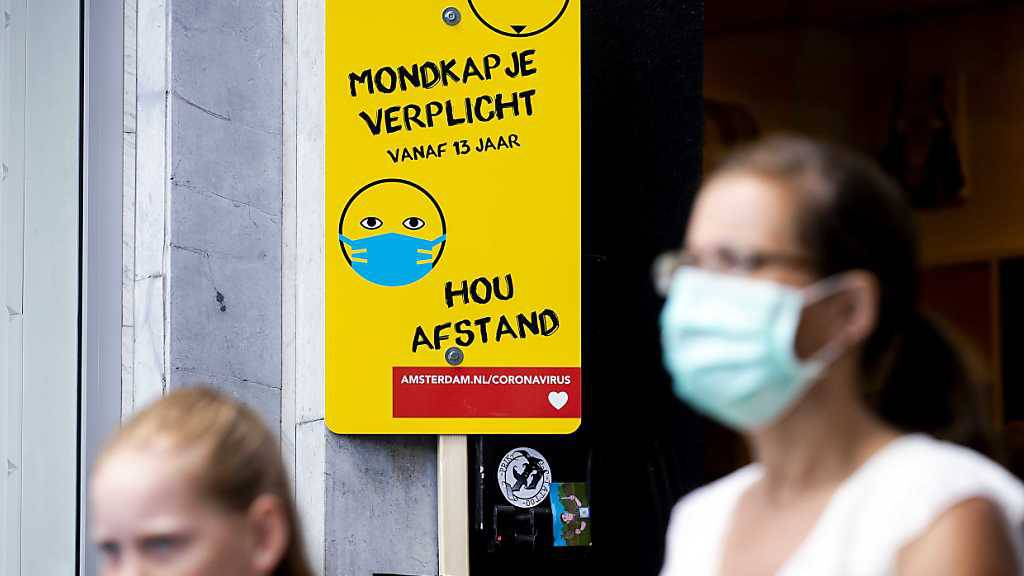 Eine Frau mit Mundschutz geht an einem Schild mit Informationen über die Maskenpflicht vorbei. Das Tragen eines Mund-Nasen-Schutzes aufgrund des Coronavirus ist an belebten Orten in Amsterdam Pflicht. Foto: sem Van Der Wal/ANP/dpa