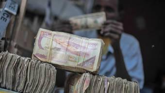 Geldwechsler in Mogadischu hinter Bündeln von Somalia-Schillings
