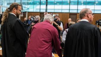 Der angeklagte Schweizer (Mitte) zusammen mit seinen Anwälten während des ersten Prozesstag vor dem Frankfurter Oberlandesgericht. Dieses sprach ihn der Spionage für schuldig. (Archivbild)
