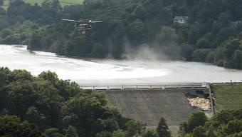 Das um 1830 gebaute Reservoir enthält rund 1,3 Millionen Tonnen Wasser. Ein Lasten-Helikopter warf grosse Säcke mit einer Mischung aus Sand, Kies und Schotter ab, um die Mauer des Reservoirs zu stabilisieren.