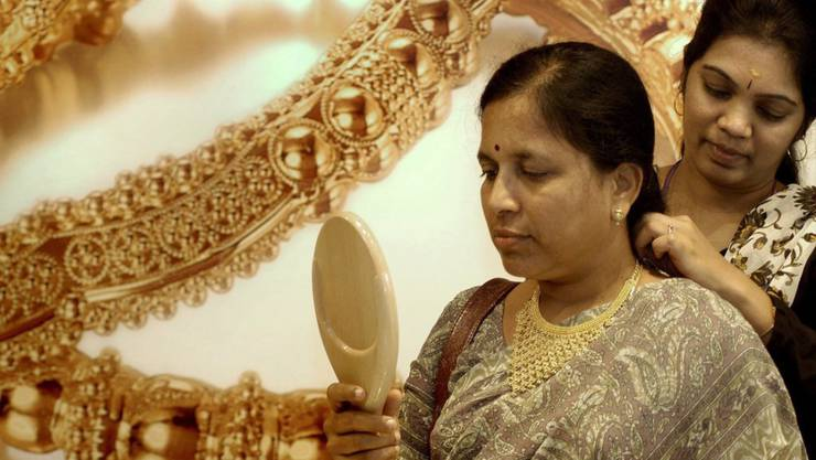Eine Verkäuferin in Indien hilft einer Kundin, eine goldene Halskette anzuprobieren. Derzeit haben Juweliere ihre Läden geschlossen, weil sie mit einem Streik gegen eine geplante Steuer auf Schmuckverkäufe protestieren wollen. (Archiv)