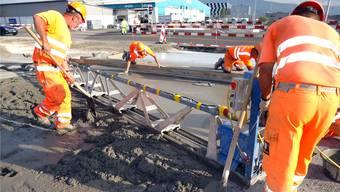 Strassenbau-Spezialisten arbeiten am Zwei-Schicht-Beton-Belag beim Schafisheimer Schoren-Kreisel.