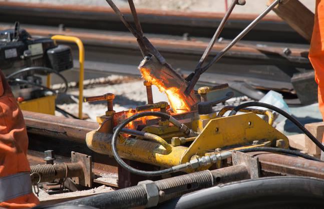 Mit Zangen entfernen die Gleisbauer den überflüssigen Stahl.