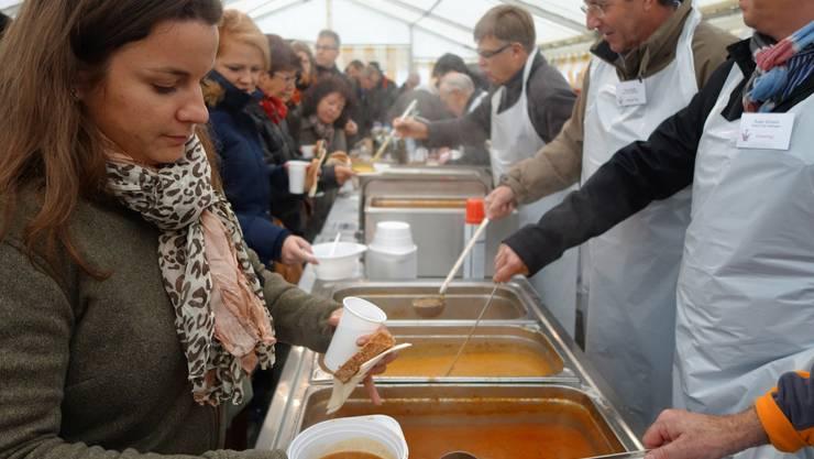 Mitglieder des Rotary Clubs verteilen Suppe an die Gäste im Zelt auf dem Wettinger Zentrumsplatz.