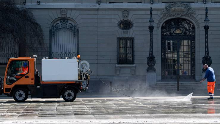 Auch die Nationalbank ist betroffen: Ein Putztrupp reinigt den Bundesplatz vor dem Gebäude der Schweizerischen Nationalbank.