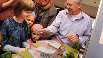 Projektleiter Christian Ammon zeigt Besucherinnen ein Modell des neuen Schulgebäudes. Juri Junkov