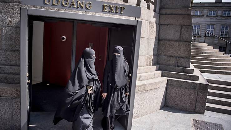 Zwei Nikab-tragende Frauen verlassen das dänische Parlament, nachdem dieses das Verbot der Vollverschleierung beschlossen hat. (Archiv)
