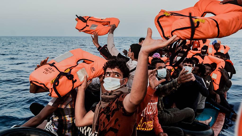 HANDOUT - Ein Helfer reicht den Bootsmigranten in einem kleinen Boot Rettungswesten. Foto: Flavio Gasperini/SOS Mediterranee/dpa - ACHTUNG: Nur zur redaktionellen Verwendung im Zusammenhang mit der aktuellen Berichterstattung und nur mit vollständiger Nennung des vorstehenden Credits