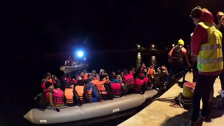 Flüchtlinge werden bei ihrer Ankunft auf der griechischen Insel Chios von Helfern in Empfang genommen.