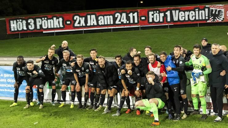 Die Spieler des FC Aarau posierten nach dem Spiel in Nyon vor dem Plakat, das unmissverständlich zum Ausdruck brachte, um was es im Moment geht: Punkte gewinnen und Ja-Stimmen bekommen.