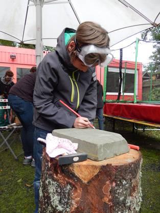 Jonas (11) zeichnet einen Zeuss-Blitz auf seinen Stein