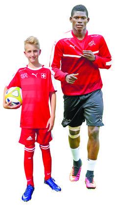 «Breel Embolo ist sehr jung und kann im Fussball noch weit kommen.» Hört man den FC-Urdorf-Junior Joel über sein Idol Breel Embolo sprechen, so könnte man meinen, hier äussere sich ein Talentsucher zum Schweizer Nati-Star. Sieben Tore werde Embolo an der EM schiessen, so sein äusserst optimistischer Tipp. Als begeisterter FCB-Fan hat Joel den Basler Stürmer auch schon live in der Arena spielen gesehen. «Embolo und dem FC Basel im Fussballstadion zuzuschauen ist sehr viel aufregender, als die Spiele im Fernsehen zu gucken», sagt der 12-Jährige, der seit sechs Jahren beim FC Urdorf spielt. Embolo sei sehr flink und könne zwischen den anderen Spielern blitzschnell hindurchdribbeln. Sieht Joel sein Idol als Ballwunder, der alle Verteidiger hinter sich lässt und ein Tor nach dem anderen schiesst? «Nein», sagt der Junior ernst. Tore schiesse eine Mannschaft, indem die Spieler einander den Ball gegenseitig zuspielen, damit am Schluss ein gut positionierter Spieler zum Abschluss kommt. «Man hat als Mannschaft sowieso viel bessere Chancen, wenn man mit den Teamkollegen zusammenspielt», sagt Joel. «Embolo macht dieses coole Spiel mit seinen Fingern, wann immer er ein Goal schiesst», weiss Joel. «Die gehen dann hin und her und rauf und runter». Manchmal nehme er nach einem Tor auch Anlauf und rutsche auf den Knien. Im Gegensatz zum Stürmer Embolo spielt Joel als rechter Verteidiger. «Mir gefällt diese Position sehr gut, ein Stürmer wie Embolo möchte ich gar nicht unbedingt sein.» Trotzdem: So wie Embolo Tore schiesst, würde er es auch gerne können. (fdu)