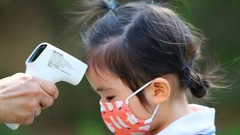 Einem Mädchen wird am ersten Tag der Wiedereröffnung einer Kindertagesstätte die Temperatur gemessen, nachdem die Kindertagesstätten der Region aufgrund der Corona-Pandemie 122 Tage geschlossen waren. Foto: -/YNA/dpa