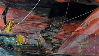 Ein Patrouillenboot versucht beim malaysischen Tanker das Öl einzudämmen
