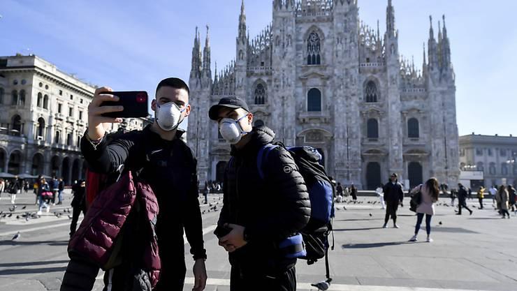 Nur noch mit Schutzmaske: Touristen vor dem Mailänder Dom. Die Hauptstadt der Lombardei ist eines der Epizentren der Coronavirus-Epidemie in Italien.