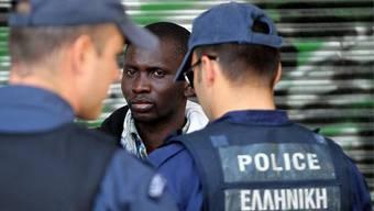 Polizisten in Athen kontrollieren einen Immigranten (Archiv)