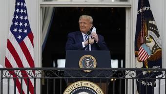 US-Präsident Donald Trump entfernt seine Gesichtsmaske, um zu seinen Anhängern zu sprechen.