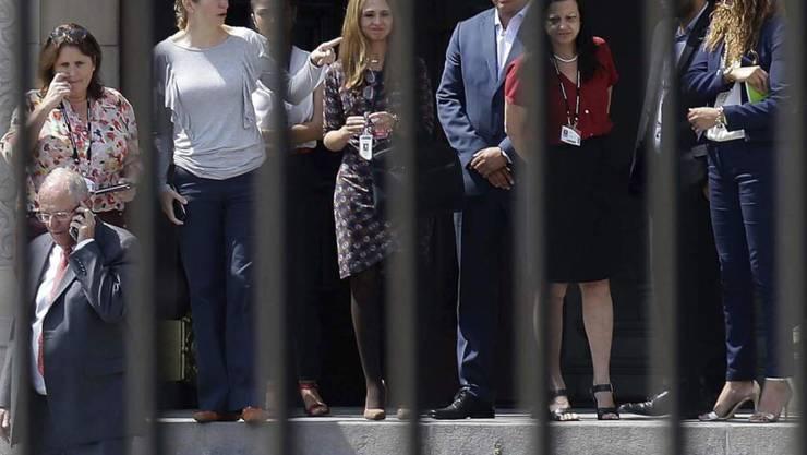 Der wegen Korruptionsvorwürfen unter Druck geratene peruanische Staatschef Pedro Pablo Kuczynski (links mit Handy) hat einen Rücktritt erklärt. Damit kam er einem für diesen Donnerstag geplanten Amtsenthebungsverfahren im Parlament zuvor.