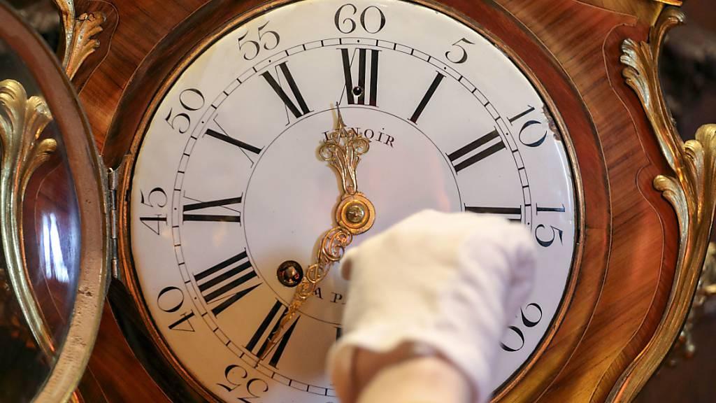 Ein Mitarbeiter kontrolliert eine Uhr im Schloss Waddesdon Manor in Buckinghamshire in Vorbereitung auf die Zeitumstellung am 25. Oktober. An diesem Sonntag werden mit Beginn der Winterzeit die Uhren in Europa wieder um eine Stunde zurückgedreht. Foto: Steve Parsons/PA Wire/dpa