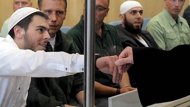 Angeklagte sitzen hinter Glasscheibe
