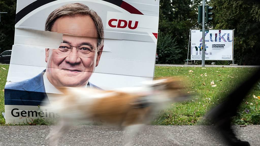 Ein Hund geht an einem beschädigten Wahlplakat vom Armin Laschet (CDU) vorbei. Foto: Federico Gambarini/dpa