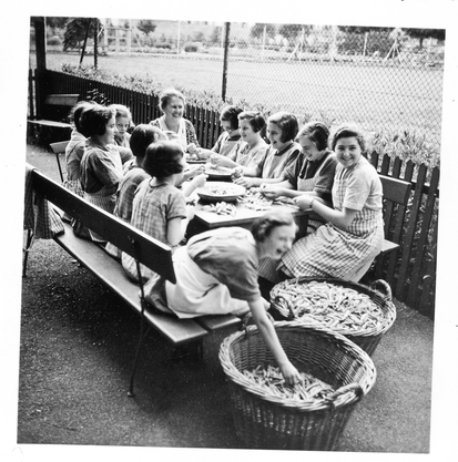 Eine Mädchengruppe rüstet Gemüse.