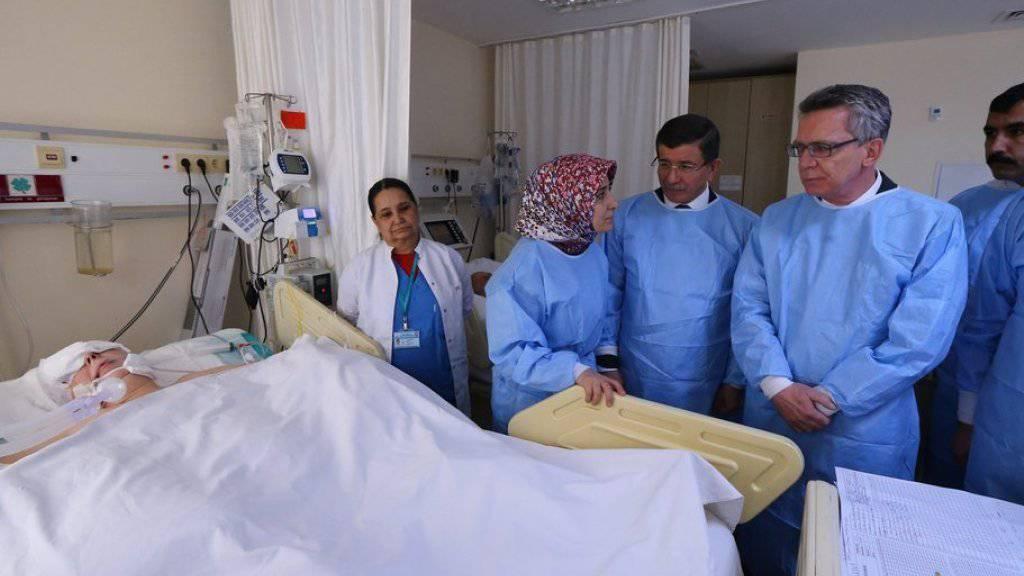 Der deutsche Innenminister Thomas de Maizière (2. von rechts) und der türkische Ministerpräsident Ahmet Davutoglu (Mitte) besuchen am Mittwoch in einem Spital in Istanbul einen Schwerverletzten.