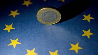 Eine Euro-Münze steht auf einer EU-Flagge (Symbolbild)