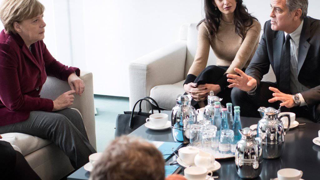 Bundeskanzlerin Angela Merkel (l) im Februar mit Amal und George Clooney. Damals besuchten die Clooneys auch eine syrische Flüchtlingsfamilie. Nun wurde ein Video davon veröffentlicht (Archiv).