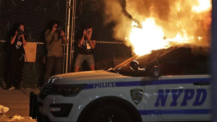 Im New Yorker Stadtteil Brooklyn setzten Demonstranten ein Polizeiauto in Brand.