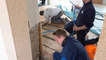 Arbeiter verlegen Kabel unter den alten Holzböden.Alex Spichale