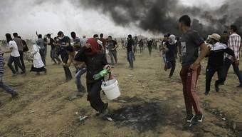 Palästinensische Demonstranten im Gazastreifen versuchen sich vor Tränengas der israelischen Armee zu retten.