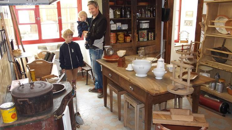 Ein Vater besichtigt mit Kindern die Küche mit altem Geschirr und Gerätschaften.