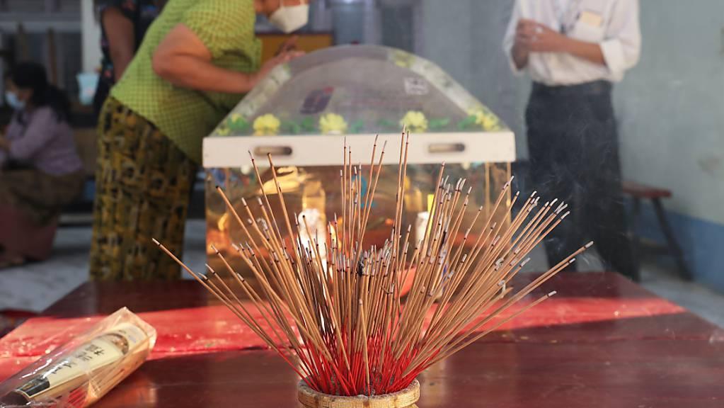 Angezündete Weihrauchstäbchen stehen auf einem Tisch im chinesischen Yunnan-Tempel, während Menschen den Leichnam von Kyal Sin betrachten. Die 20-jährige Studentin wurde während einer Demonstration gegen den Putsch der Militärjunta von Polizisten mit einem Kopfschuss getötet. Foto: Uncredited/AP/dpa