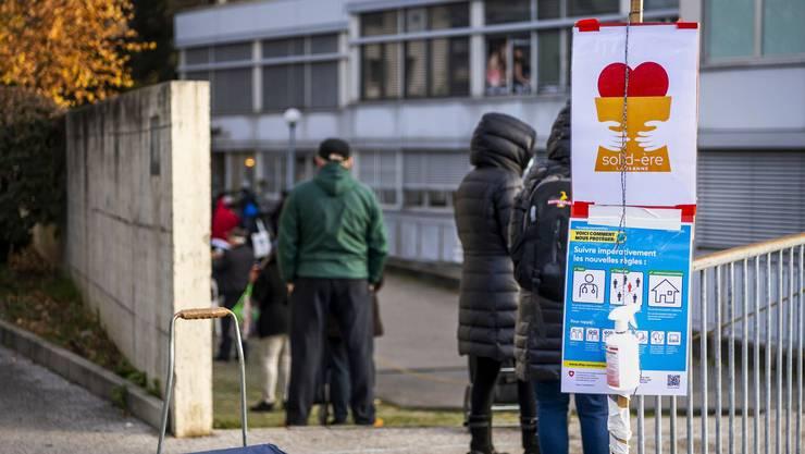 Hilfsbedürftige warten in Lausanne vor der Ausgabe in der Schlange.