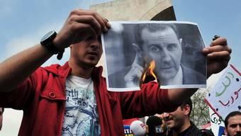 In Istanbul verbrennt ein Gegner von Baschar al-Assad ein Foto des Herrschers