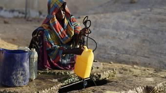 Eine Frau holt Wasser aus einem tiefen Brunnen. In Somalia treibt eine schwere Dürre Menschen in die Flucht - und hat bereits mehrere Todesopfer gefordert. (Archiv)